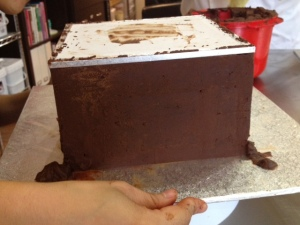 Flip the cake upside down to the board covered with ganache to work on the top